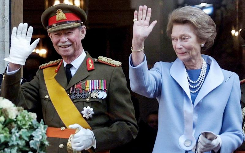Grand Duke Jean of Luxembourg and his wife wave to the crowd at the end of his 36-year reign. - AFP