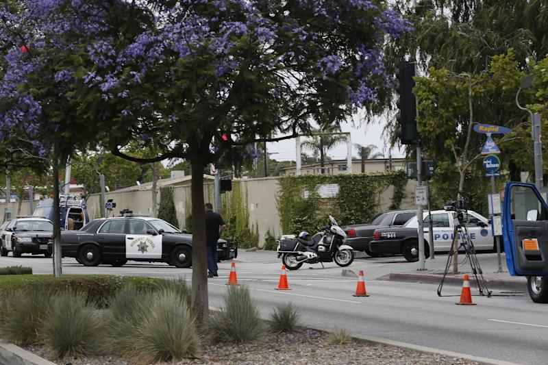 Police stand outside the locked down Santa Monica College campus in Santa Monica, Calif. Friday, June 7, 2013. Two people were found dead Friday in a burned home near the school, where someone sprayed a street corner with gunfire, wounding at least three people, authorities said. (AP Photo/Damian Dovarganes)