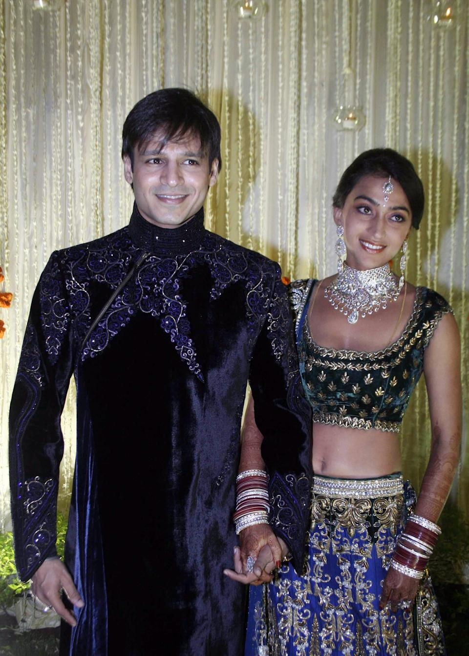 Indian Bollywood actor Vivek Oberoi (L) recently married Priyanka Alva (R) pose at a reception party late night October 31, 2010 in Mumbai. AFP PHOTO/STR (Photo credit should read STRDEL/AFP via Getty Images)
