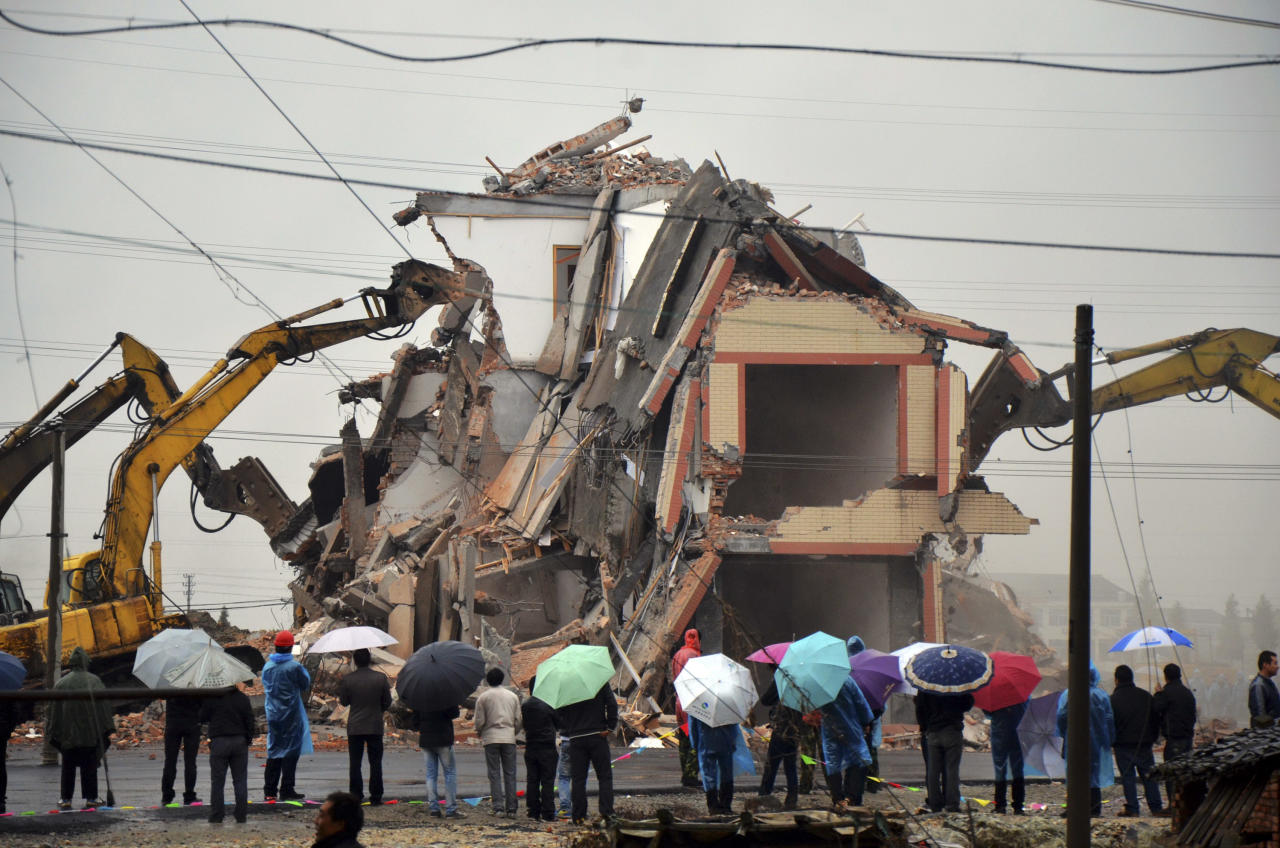 A house in the middle of a new road is torn down on the outskirts of Wenling city, in eastern China's Zhejiang province, Saturday, Dec. 1, 2012. Authorities have demolished the five-story home that stood incongruously in the middle of the new main road and had become the latest symbol of resistance by Chinese homeowners against officials accused of offering unfair compensation. (AP Photo) CHINA OUT