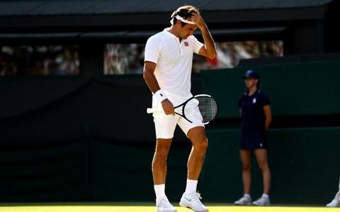 Roger Federer of Switzerland wipes his forehead against Kevin Anderson of South Africa during their Men's Singles Quarter-Finals match on day nine of the Wimbledon Lawn Tennis Championships at All England Lawn Tennis and Croquet Club on July 11, 2018 in London, England.  - Credit: Getty Images
