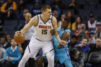 Denver Nuggets center Nikola Jokic, left, drives into Charlotte Hornets guard Terry Rozier during the first half of an NBA basketball game in Charlotte, N.C., Thursday, March 5, 2020. (AP Photo/Nell Redmond)