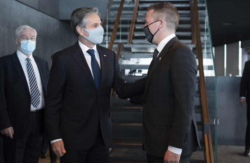 Icelandic Foreign Minister Gudlaugur Thor Thordarson, centre right, greets US Secretary of State Antony Blinken as he arrives for meetings at the Harpa Concert Hall in Reykjavik, Iceland, Tuesday, May 18, 2021. Blinken is touting the Biden administration's abrupt shift in its predecessor's climate policies as he visits Iceland for talks with senior officials from the world's Arctic nations. (Saul Loeb/Pool Photo via AP)
