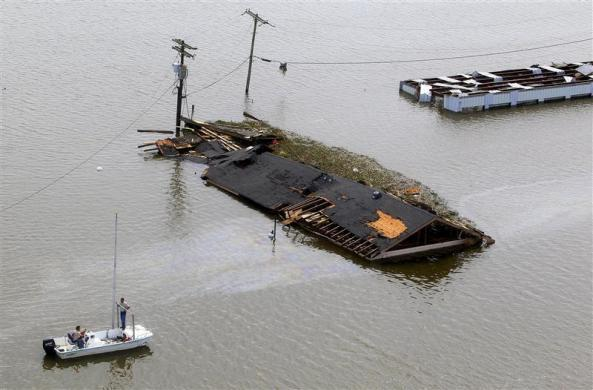 Officials assess the damage as houses are partially submerged in flood waters after a Hurricane Isaac levee breach in Braithwaite, Louisiana August 31, 2012.