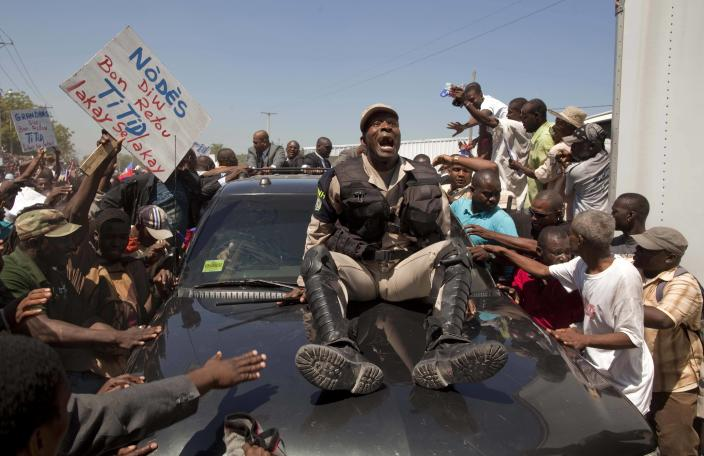 A police officer rides on the hood of the vehicle carrying Haiti's former President Jean-Bertrand Aristide as he arrives to his home in Port-au-Prince, Haiti, Friday March 18, 2011. Aristide, who was forced to flee Haiti due to a rebellion in 2004 aboard a U.S. plane, returned after seven years of exile in South Africa, days before Haiti's presidential runoff election Sunday.