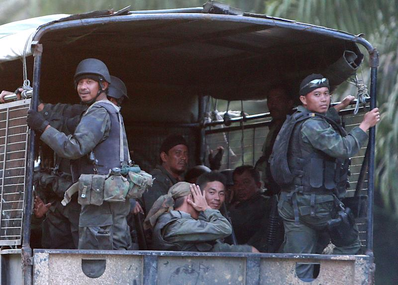 Malaysian army commandos in the back of their truck move on the way to join an assault near the area where a stand-off with Filipino gunmen took place, in Tanduo village, Lahad Datu, Borneo's Sabab state, Malaysia on March 5, 2013. Malaysia launched airstrikes and mortar attacks against nearly 200 Filipinos occupying a Borneo coastal village Tuesday to end a bizarre three-week siege that turned into a security nightmare for both Malaysia and the Philippines. (AP Photo) MALAYSIA OUT, NO SALES, NO ARCHIVES