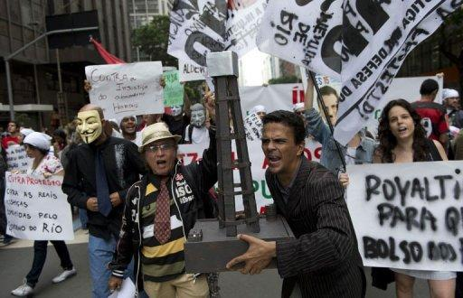 <p>People shout slogans during a demonstration in Rio demanding Brazilian President Dilma Roussef veto a bill that would redistribute oil royalties in favor of non-oil producing states.</p>