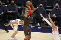 Portland Trail Blazers' Gary Trent Jr. puts up a shot against the Phoenix Suns' Frank Kaminsky III as Devin Booker looks on during the first half of an NBA basketball game Monday, Feb. 22, 2021, in Phoenix. (AP Photo/Darryl Webb)