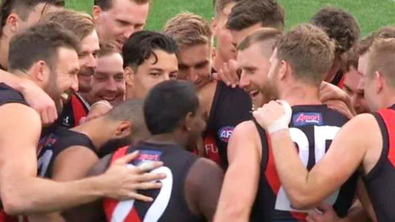Essendon players laugh at a joke in a team huddle.
