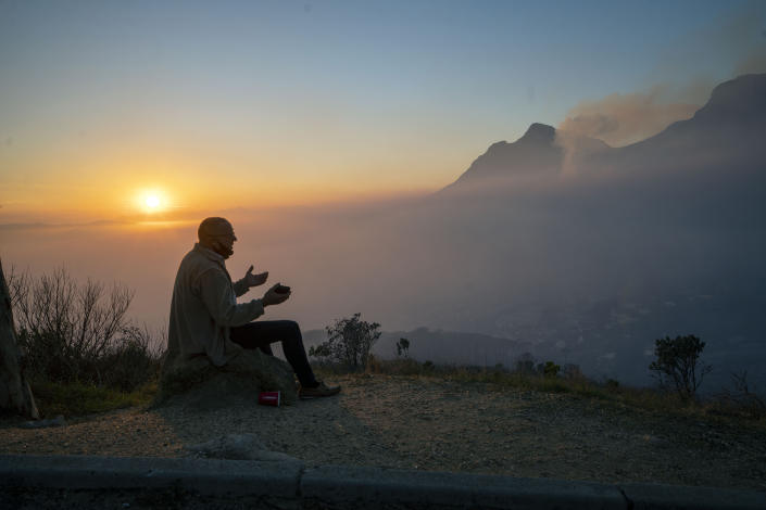 A Capetonian watches the sun rise from the top of Signal Hill as smoke engulfs the city of Cape Town, South Africa, Tuesday April 20, 2021. A massive fire spreading on the slopes of the city's famed Table Mountain, at right, is kept under control as firemen and helicopters take advantage of the low winds to contain the blaze. (AP Photo/Jerome Delay)