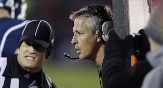 Connecticut interim head coach T.J. Weist, center, listens to an official during the first half of an NCAA college football game against Louisville, in East Hartford, Conn., Friday, Nov. 8, 2013. (AP Photo/Charles Krupa)