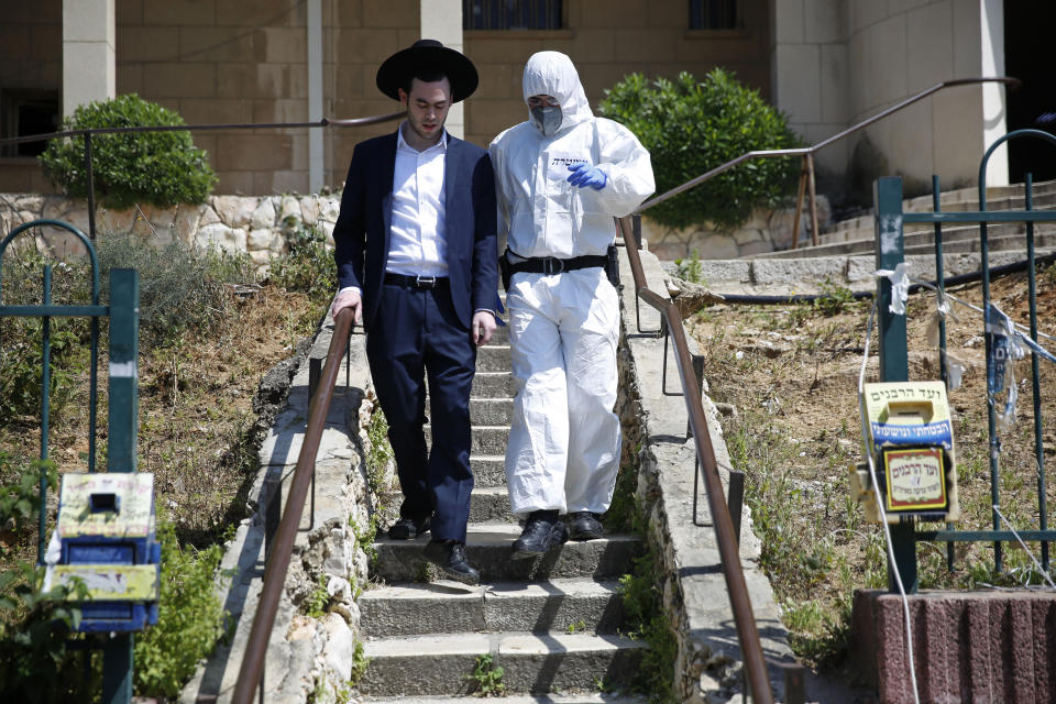 An Israeli police officer wearing protective gear detains an ultra-Orthodox man after he prayed in a synagogue in defiance of government measures to help stop the spread of the coronavirus, in Bnei Brak, a suburb of Tel Aviv, Israel, Thursday, April 2, 2020. On Wednesday, Israeli Prime Minister Benjamin Netanyahu ordered a police cordon around the largely ultra-Orthodox city of Bnei Brak, to limit movement to and from the city. Bnei Brak has the second highest number of coronavirus cases in Israel. (AP Photo/Ariel Schalit)