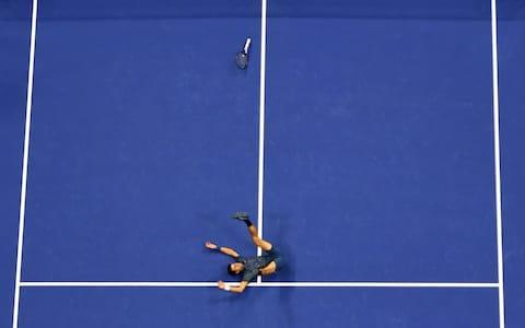 <span>Novak Djokovic falls to the court in celebration after his victory over Juan Martin del Potro</span> <span>Credit: AFP </span>