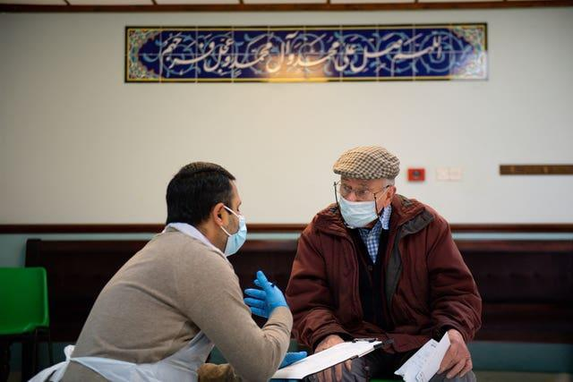 A member of the public is spoken to by a volunteer before receiving an injection of the Oxford/AstraZeneca coronavirus vaccine at the Al Abbas Mosque, Birmingham (Jacob King/PA)