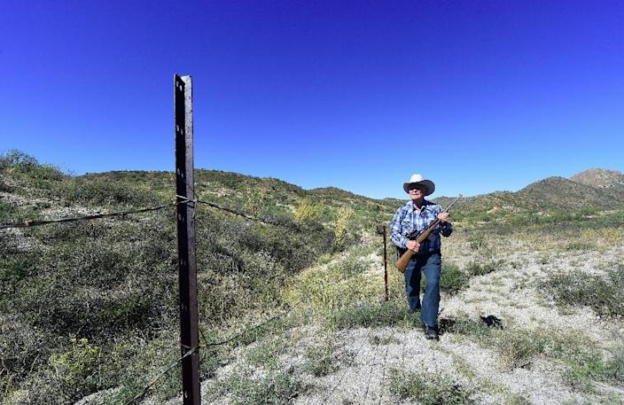 Cattle rancher Jim Chilton walks beside a fence that is the US-Mexico border on part of his 50,000 acre ranch southeast of Arivaca, Arizona (AFP Photo/Frederic J. Brown)