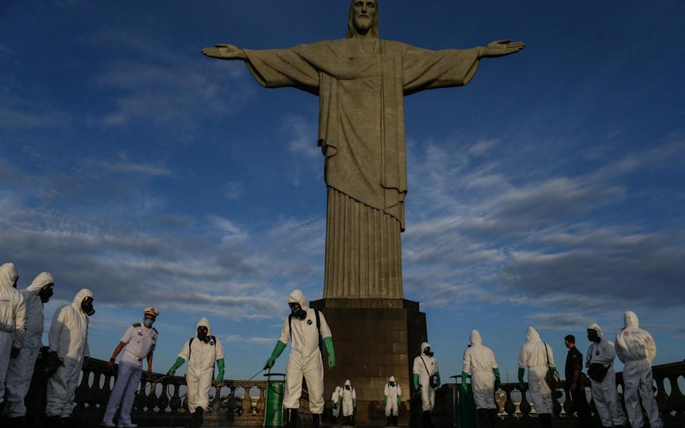 Pictured last year, military personnel in Rio disinfect the area around the Christ the Redeemer statue - Getty