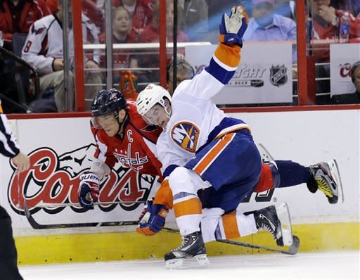 Washington Capitals left wing Alex Ovechkin (8), from Russia, is hit by New York Islanders defenseman Thomas Hickey (14) during the second period of an NHL hockey game Tuesday, March 26, 2013, in Washington. (AP Photo/Alex Brandon)
