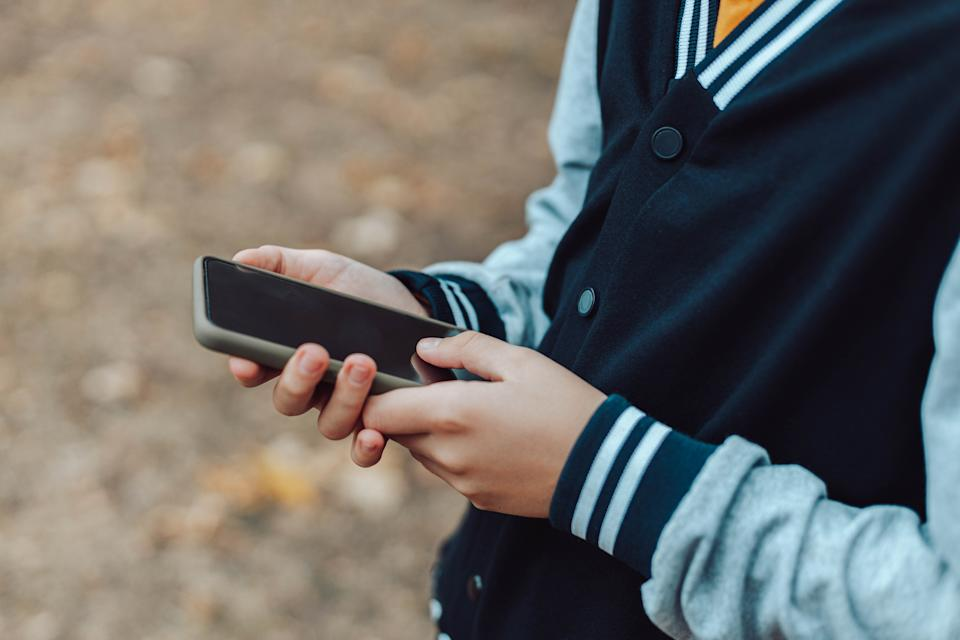Child hands uses smartphone in summer park, looking at screen of devices