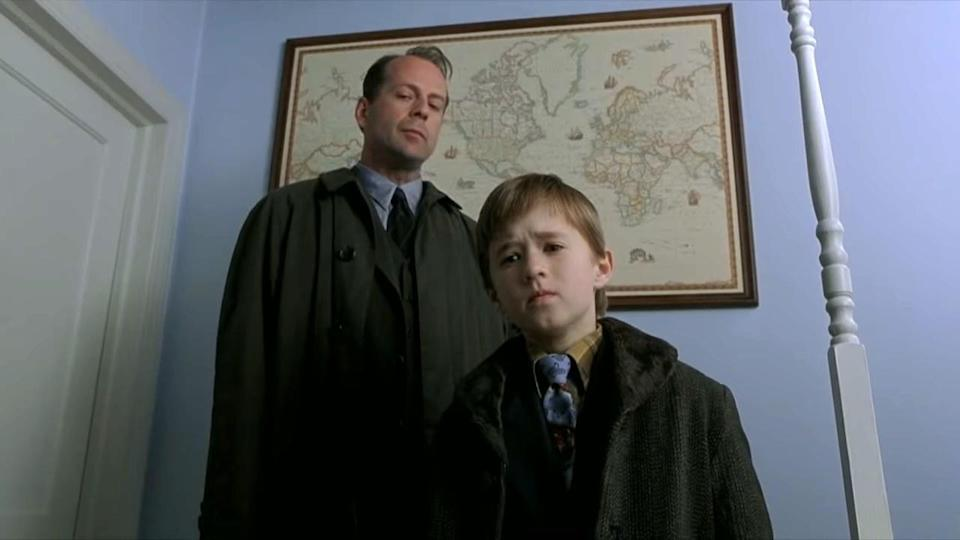 Bruce Willis and Haley Joel Osment look down at something with concern