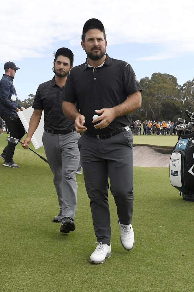 Mexico's Abraham Ancer, left, and Roberto Diaz walk off the 18th green during the World Cup of Golf in Melbourne, Australia, Sunday, Nov. 25, 2018. (AP Photo/Andy Brownbill)