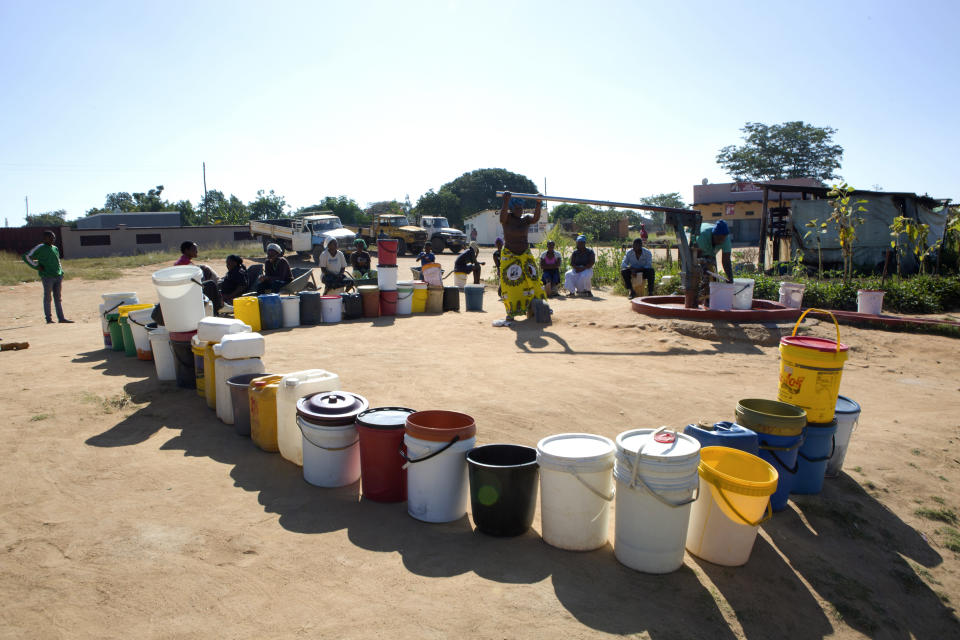 In this March, 31, 2020, photo, buckets are lined up as women fetch water in a suburb of Harare, Zimbabwe. For people around the world who are affected by war and poverty, the simple act of washing hands is a luxury, even during the coronavirus pandemic. In Zimbabwe, clean water is often saved for daily tasks like doing dishes and flushing toilets. (AP Photo/Tsvangirayi Mukwazhi)