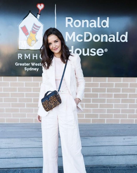 A photo of actor Katie Holmes standing in front of a sign at Ronald McDonald House Westmead.