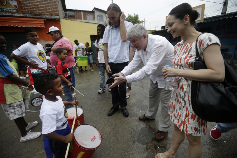 Royal Opera House Chief Executive Anthony William Hall, second from right, and Brazilian dancer of London's Royal Ballet Roberta Marquez, right, greet children as they visit the Afro Reggae cultural center in the Vigario Geral slum of Rio de Janeiro, Brazil, Saturday, March 2, 2013. This past week Royal Ballet dancers shared their knowledge and advice with promising artists during an education symposium between the company and the cultural arts center Afro Reggae. (AP Photo/Silvia Izquierdo)
