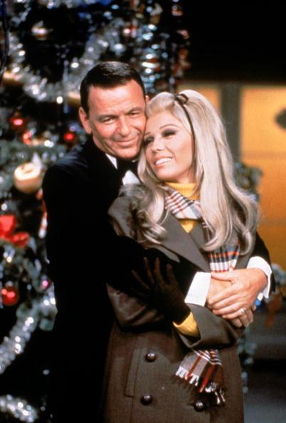 """<div class=""""caption-credit""""> Photo by: Martin Mills/Getty Images</div><b>With her dad, Frank Sinatra, in the late '60s</b> <br> The warm mens-style coat and plaid scarf would still work today, but we love how Nancy kept things girly with a thin bow in her hair. Nowadays a bow like that is typically seen on the under-five set, but we're going to experiment. <br>"""
