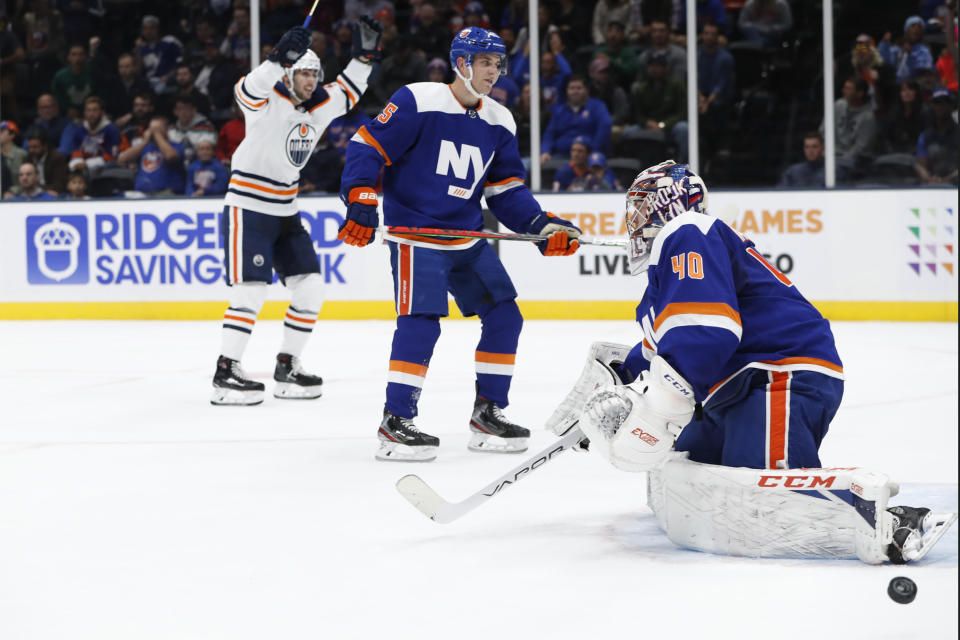 Edmonton Oilers left wing James Neal, left, celebrates after scoring a goal on New York Islanders goaltender Semyon Varlamov (40) during the first period of an NHL hockey game Tuesday, Oct. 8, 2019, in Uniondale, N.Y. Islanders defenseman Devon Toews is between Neal and Varlamov. Neal had two goals in the period. (AP Photo/Kathy Willens)
