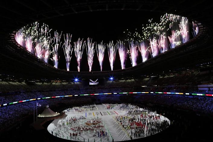 The Tokyo Olympics opening ceremony is illuminated by fireworks.