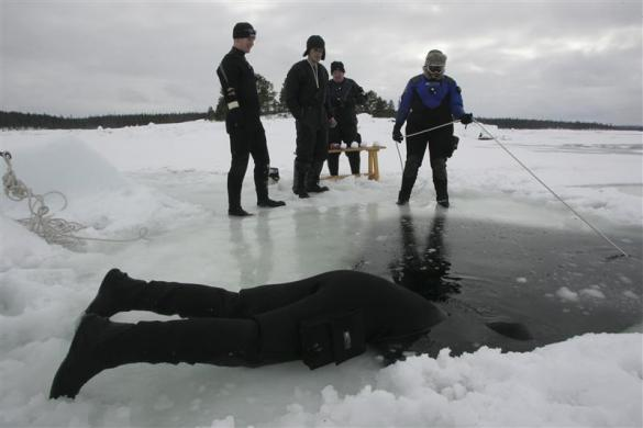 A diver, half immersed in water, checks on another diver during an ice-diving session on the coast of the White Sea near the village of Nilmaguba in the north of Russia's Karelia region April 7, 2006.