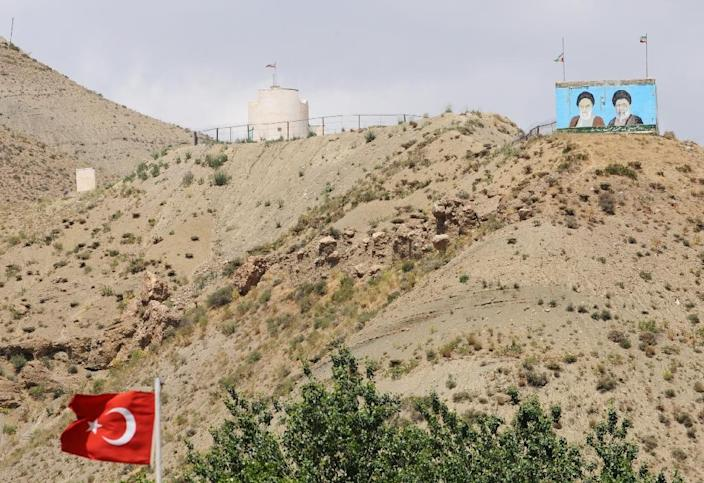 Supreme leaders of Iran, the late Ayatollah Ruhollah Khomeini (L) and Ayatollah Ali Khameni (R), are seen on the top of a hill from the Turkish side of the border near the Esendere crossing between Turkey and Iran on June 25, 2012 in Yuksekova (AFP Photo/Bulent Kilic)