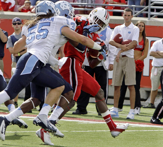 Louisville running back Senorise Perry fights to break free of North Carolina defenders Sam Smiley (3) and Tommy Heffeman (55) to get to the end zone to score a touchdown during the first half of an NCAA college football game in Louisville, Ky., Saturday, Sept. 15, 2012. (AP Photo/Garry Jones)