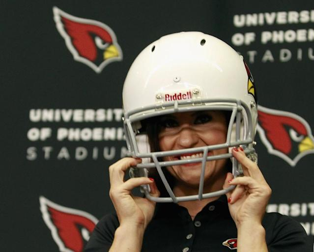 Jen Welter puts on a Arizona Cardinals helmet after being named an intern coach to the team during a press conference on July 28, 2015 in Tempe, Arizona (AFP Photo/Ralph Freso)