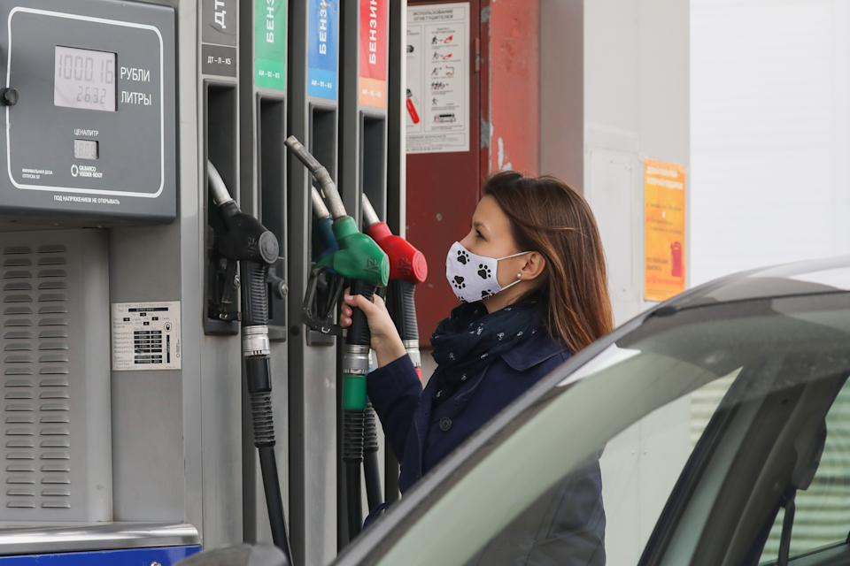 RYAZAN, RUSSIA: A woman fills up at a petrol station. The wholesale petrol price has dropped due to the decrease in demand at Russian fuel filling stations amid the self-isolation regime. (Photo: Alexander Ryumin\TASS via Getty Images)