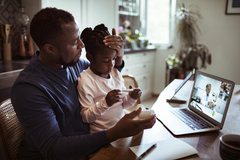 Close up of a father and daughter having a video call with their doctor
