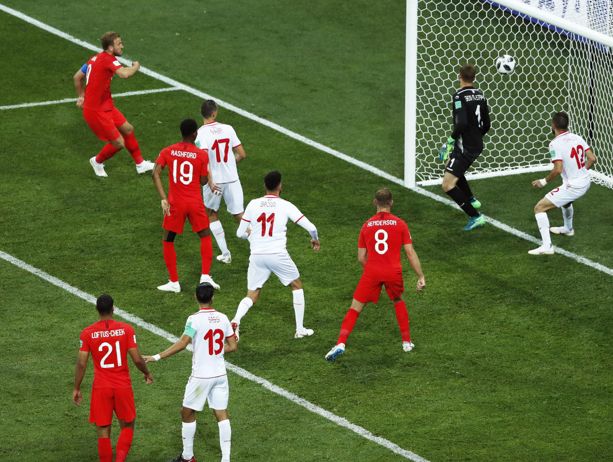 England's Harry Kane, left, scores his side's winning goal during the group G match between Tunisia and England at the 2018 soccer World Cup in the Volgograd Arena in Volgograd, Russia, Monday, June 18, 2018. (AP Photo/Rebecca Blackwell)