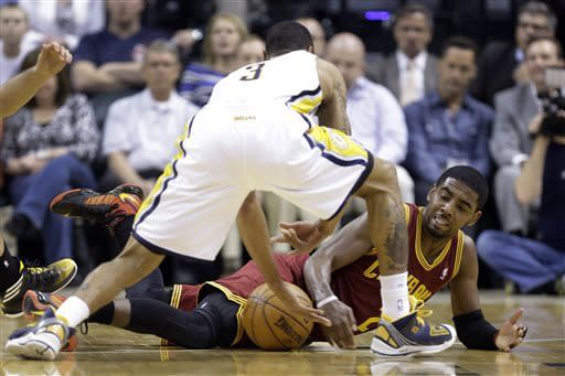 Cleveland Cavaliers guard Kyrie Irving, bottom, looks to grab a loose ball in front of Indiana Pacers guard George Hill in the first half of an NBA basketball game in Indianapolis, Tuesday, April 9, 2013. (AP Photo/Michael Conroy)