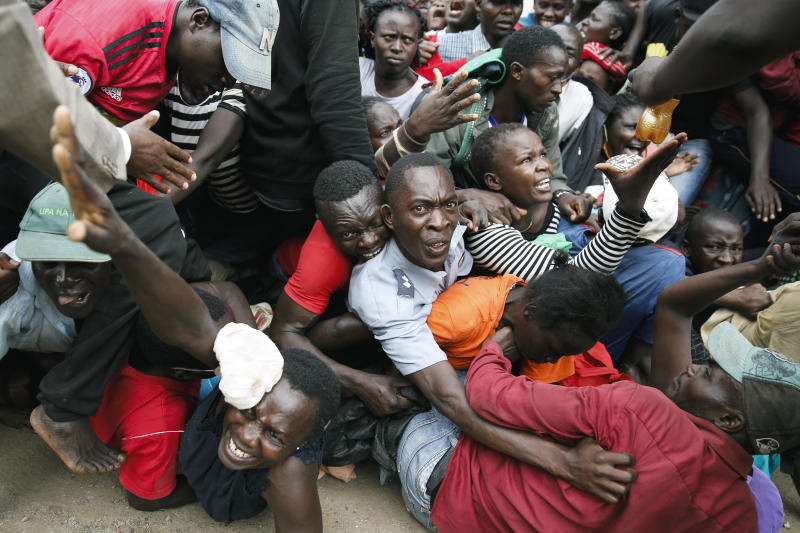 Residents desperate for a planned distribution of food for those suffering under Kenya's coronavirus-related movement restrictions push through a gate and create a stampede, causing police to fire tear gas and leaving several injured, at a district office in the Kibera slum, or informal settlement, of Nairobi, Kenya, Friday, April 10, 2020. (AP Photo/Brian Inganga)