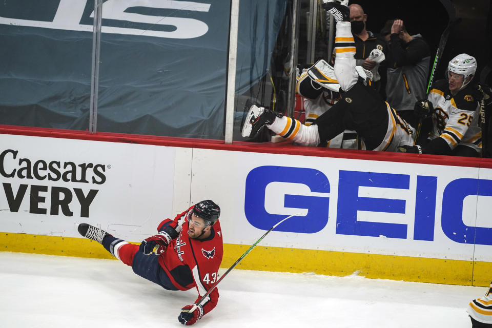 Washington Capitals right wing Tom Wilson (43) falls to the ice after checking Boston Bruins center Curtis Lazar (20) into his bench during the first period of Game 2 of an NHL hockey Stanley Cup first-round playoff series Monday, May 17, 2021, in Washington. (AP Photo/Alex Brandon)