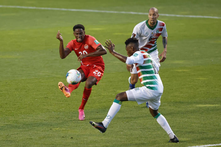 Canada's Jonathan David (20) tries to score past Suriname's Kelvin Leerdam (18) during the first half of a World Cup 2022 Group B qualifying soccer match Tuesday, June 8, 2021, in Bridgeview, Ill. (AP Photo/Kamil Krzaczynski)