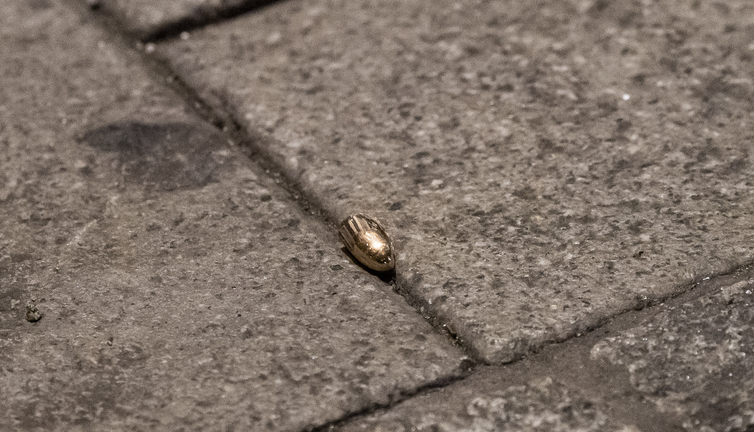 A bullet lies on the sidewalk near a restaurant at the scene of a shooting in central Hanau, Germany Thursday, Feb. 20, 2020. Eight people were killed in shootings in the German city of Hanau on Wednesday evening, authorities said. (Andreas Arnold/dpa via AP)