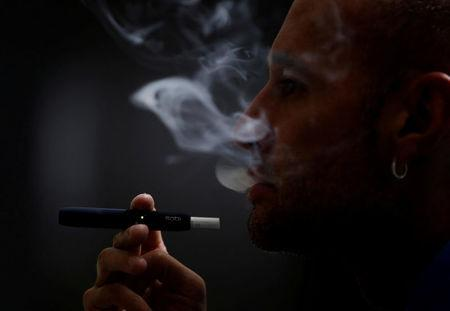 FILE PHOTO: A man poses for a photograph while using a Philip Morris iQOS smoking device, in Bogota, Colombia November 14, 2017.  REUTERS/Jaime Saldarriaga/File Photo