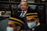 Malaysia's Prime Minister Muhyiddin Yassin reacts during a session of the lower house of parliament, in Kuala Lumpur