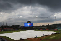 Toronto Blue Jays grounds crew members roll out a tarp to protect the field from rain during the fourth inning of a baseball game against the Tampa Bay Marlins, Saturday, Aug. 15, 2020, in Buffalo, N.Y. (AP Photo/Jeffrey T. Barnes)