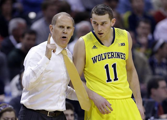 Michigan head coach John Beilein, left, talks to Michigan guard Nik Stauskas (11) in the first half of an NCAA college basketball game against Michigan State in the championship of the Big Ten Conference tournament on Sunday, March 16, 2014, in Indianapolis. (AP Photo/Michael Conroy)