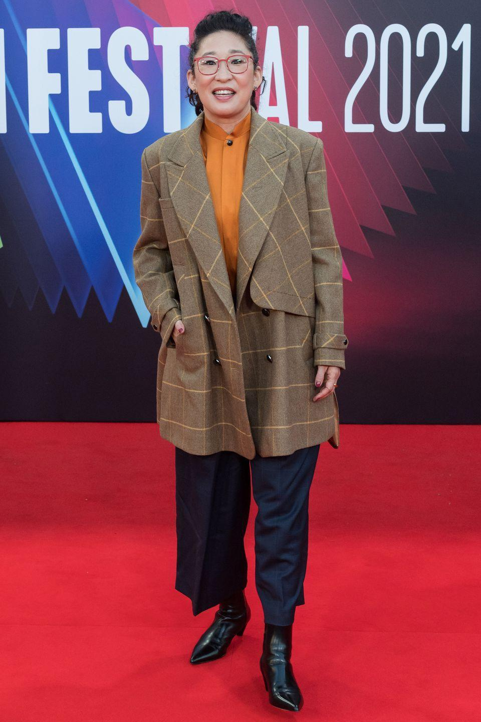 <p><strong>10 October</strong></p><p>Sandra Oh attended the premiere of The French Dispatch at the film festival, wearing a checked jacket and wide-leg trousers.</p>