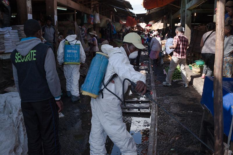 Government workers spray disinfectant during cleanup of a market in Antananarivo, the capital of Madagascar, on Oct. 10. (RIJASOLO/AFP via Getty Images)