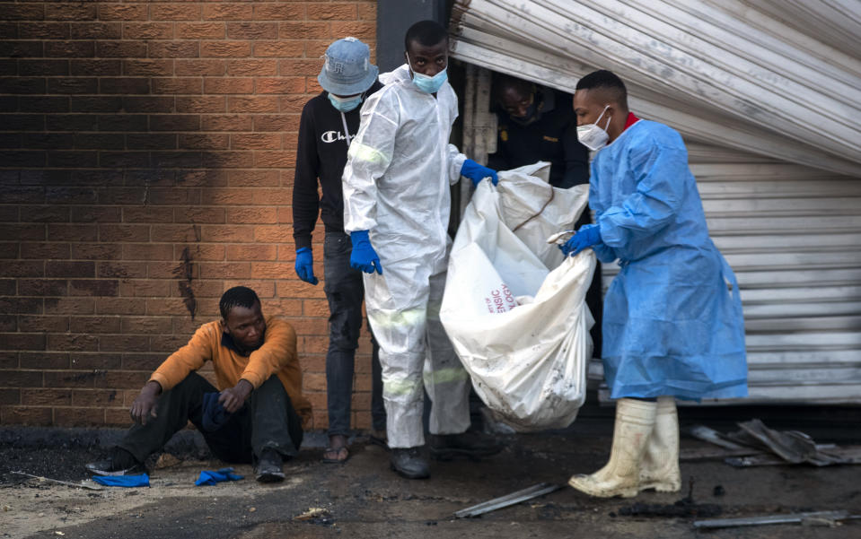 A family member watches on as police forensics officers carry the body his brother who was found inside a burned shop, in Johannesburg, South Africa, Sunday, July 11, 2021. Protests have spread from the KwaZulu Natal province to Johannesburg against the imprisonment of former South African President Jacob Zuma who was imprisoned last week for contempt of court. (AP Photo/Themba Hadebe)