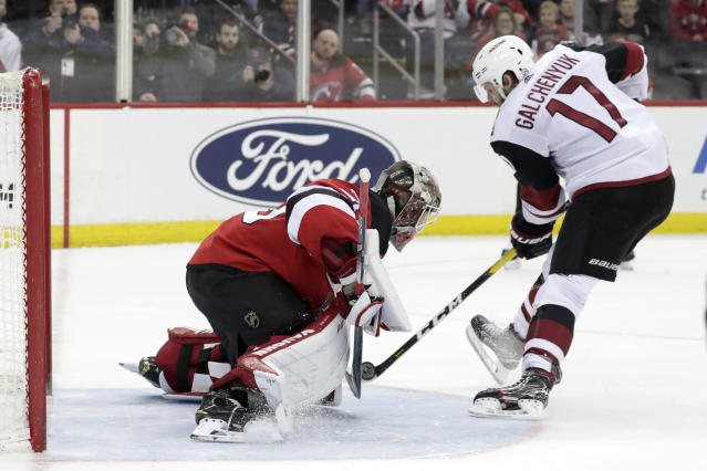 New Jersey Devils goaltender MacKenzie Blackwood, left, blocks a shootout shot by Arizona Coyotes center Alex Galchenyuk (17) during an NHL hockey game, Saturday, March 23, 2019, in Newark, N.J. The Devils on 2-1 in a shootout. (AP Photo/Julio Cortez)